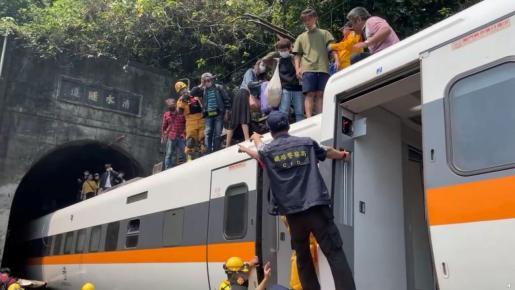 El equipo de rescate ayudando a salir a los pasajeros de los vagones.