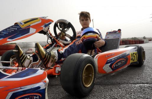 El piloto mallorquín Edu Robinson Lliteras posa sobre un kart en el circuito de Ca'n Picafort.