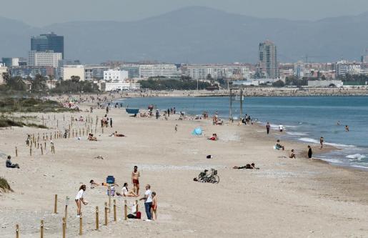 Cientos de personas pasean y toman en sol en las playas de la Dehesa de El Saler, en Valencia, hoy Sábado Santo, en el que las temperaturas rondan los 25 grados.