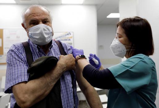 Una sanitaria vacuna a una persona mayor en un ambulatorio de Valencia. La Comunidad Valenciana ha proseguido la pauta de vacunación a los mayores de 80 años, este Viernes Santo.