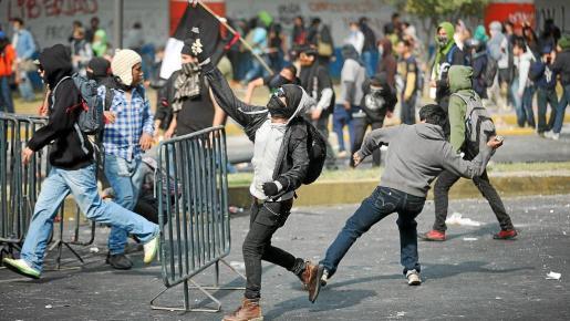 Jóvenes activistas se enfrentan a policías en las inmediaciones del Palacio Legislativo de México antes de la toma de posesión de Peña Nieto.