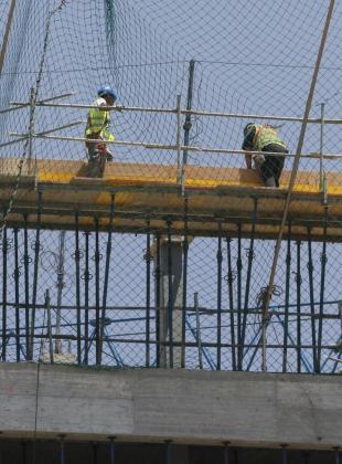 Dos obreros trabajan en una construcción.