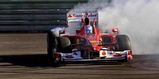 El piloto español de la escudería Ferrari, Fernando Alonso, saluda a los aficionados desde el interior de su monoplaza este mediodía en la pista del Circuito Ricardo Tormo de Cheste (Valencia).