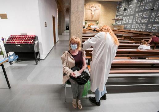 Una mujer recibe una dosis de la vacuna de AstraZeneca en una iglesia zaragozana.
