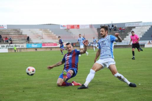 El delantero del Poblense Aitor Pons intenta interceptar un pase del defensa del Atlético Baleares Cristian en un momento del partido que enfrentó a ambos equipos en el Municipal de sa Pobla.