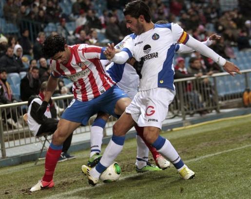 El delantero brasileño del Atlético de Madrid Diego Costa (i) pelea un balón con Miguel Torres (d), del Getafe, durante el partido de ida de los octavos de la final de la Copa del Rey que están disputando esta noche en el estadio Vicente Calderón