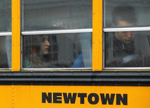 Estudiantes cabizbajos acuden en un autobús escolar de Newtown a un colegio de la zona para reanudar las clases, cuatro días después de la matanza.