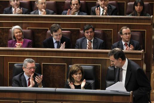 El presidente del Gobierno, Mariano Rajoy (abajo - d), recibe los aplausos de la vicepresidenta, Soraya Sáenz de Santamaría (abajo - c), del ministro de Justicia, Alberto Ruiz-Gallardón (abajo - i), y del resto de diputados de su partido, tras su intervención en la sesión de control al Ejecutivo, esta mañana en el Congreso de los Diputados.