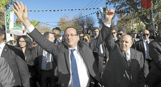 François Hollande, junto al presidente de Argelia, Abdelaziz Bouteflika, saluda a la multitud mientras camina por el Place Maurice-Audin de Argel.