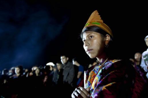 Una mujer indígena participa en un ceremonia maya despidiendo el ultimo sol de esta era y preparando para recibir el Baktun13, en el sitio arqueológico Mixco Viejo, localidad de San Martín Jilotepeque, en el departamento de Chimaltenango (Guatemala).