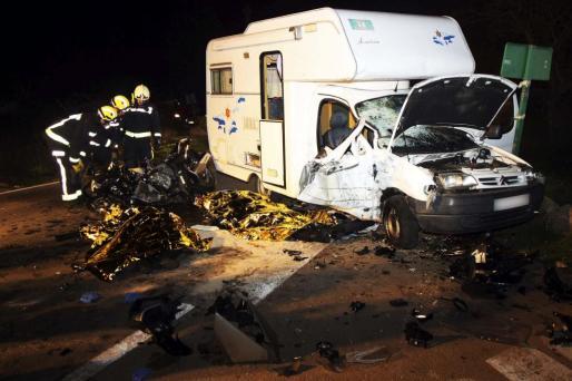 Tres bomberos examinan la escena del accidente, donde yacen los dos motoristas sin vida junto a la autocaravana.