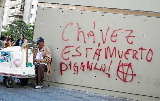 Un hombre vende helados junto a un graffiti que especula con la muerte del presidente.