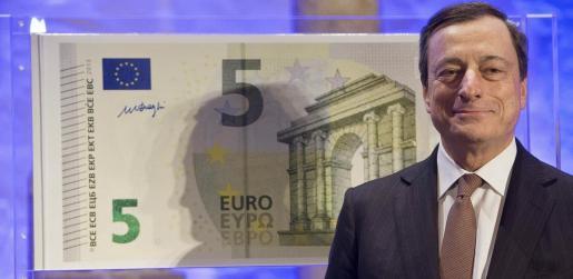 El presidente del Banco Central Europeo (BCE), Mario Draghi, posa al lado de una copia a tamaño gigante del nuevo billete de cinco euros, en Fráncfort, Alemania hoy, jueves 10 de enero de 2013. El nuevo billete de 5 euros entrará en circulación en mayo y tiene tres marcas de seguridad nuevas. EFE/Boris Roessler