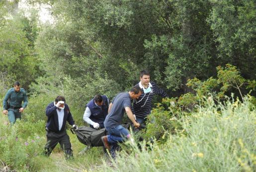 Agentes de la Guardia Civil y operarios de la funeraria trasladan el cadáver.