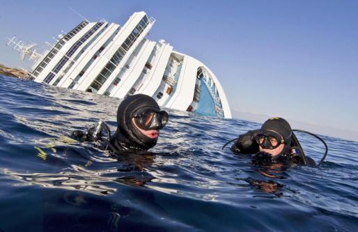 """Buceadores de los """"Carabiniari"""" italianos en el agua cerca del crucero """"Costa Concordia""""."""