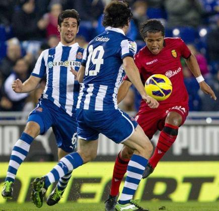 El defensa argentino del Espanyol Juan Forlin (i) y su compañero, el defensa argentino Diego Colotto (c), disputan un balón con el delantero mexicano del Mallorca Giovani Dos Santos (d), durante el partido disputado hoy en Barcelona.