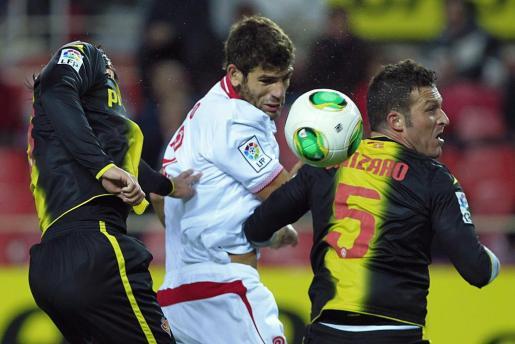 El defensa argentino del Sevilla Federico Julián Fazio (c) y los jugadores del Zaragoza, el rumano Ionut Cristian Sapunaru (i) y el italiano Maurizio Lanzaro luchan por el balón durante el partido de vuelta de cuartos de final de la Copa del Rey.