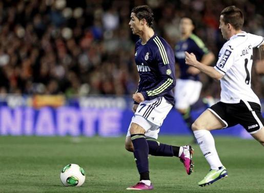 El defensa portugués del Valencia Joao Pereira (d) persigue al delantero portugués del Real Madrid Cristiano Ronaldo, durante el partido correspondiente a la vuelta de los cuartos de final de la Copa del Rey de fútbol que se disputa esta noche en el estadio de Mestalla.