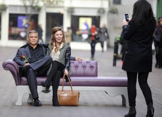 Una mujer posa junto a la figura de cera del actor George Clooney del Madame Tussauds expuesto en Carnaby Street en Londres (Reino Unido) con motivo del Día de San Valentín hoy, miércoles 13 de febrero de 2013.