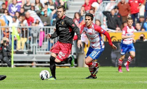 Antonio Luna avanza con el balón controlado sobre el césped del Nuevo Los Cármenes mientras es perseguido por Recio, centrocampista del Granada.