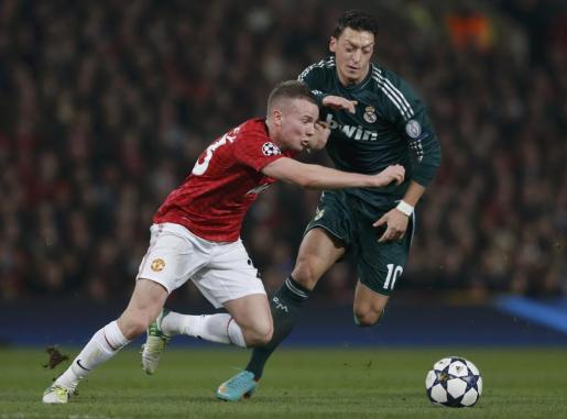 El jugador del Manchester United, Tom Cleverley (izq.), en una jugada con el madridista Ozil.