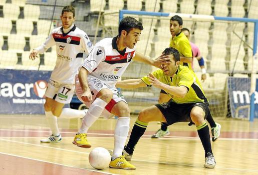 Un jugador del Santiago Futsal intenta zafarse de la defensa de un efectivo del Fisiomedia Manacor.