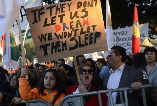 """Una manifestante protesta y muestra una pancarta en la que se puede leer """"si ellos no nos dejan soñar, nosotros no les dejaremos dormir"""", durante una concentración contra el impuesto sobre los depósitos."""