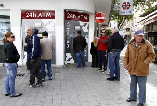 Un grupo de personas hace cola junto al cajero automático de una sucursal cerrada del banco Laiki, en Nicosia, Chipre.