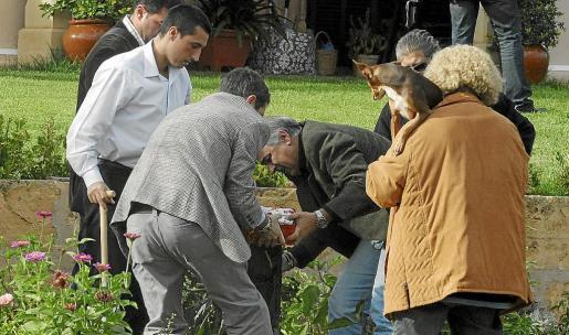 Momento en el que la Policía Judicial saca de la huerta de Antònia Ordinas, en Pòrtol, la lata llena de dinero en efectivo.