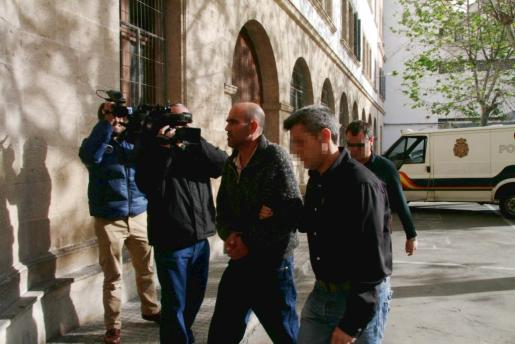 Andrés R.G., en el centro, es conducido a los juzgados de Palma.
