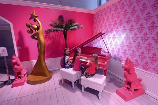 """Tres niñas tocan un piano rosa en el interior de una de las salas de la recién inaugurada """"Barbie Dreamhouse Experience""""."""
