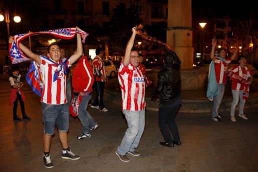 La Plaça Joan Carles I se convierte en el escenario de las celebraciones atléticas en la Isla –izquierda y centro– mientras Neptuno –derecha– se inundaba de hinchas.