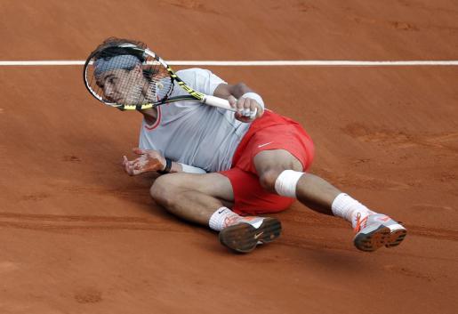 El tenista español Rafael Nadal cae al suelo durante el partido de cuartos de final del torneo de Roland Garros disputado frente al suizo Stanislas Wawrinka.