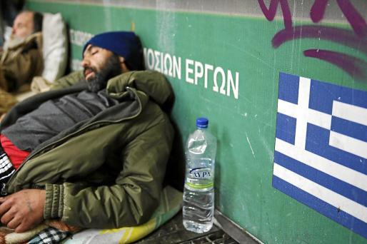 Dos griegos sin techo duermen en la entrada de la estación del metro de Atenas.