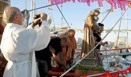El patrón de la barriada, Sant Antoni, en el momento de ser izado en el velero de época porteador «Alcatraz».