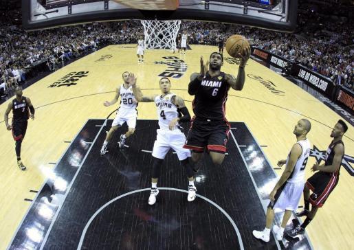 El jugador de los Heat LeBron James (centro dcha) salta para encestar ante la mirada de Danny Green (centro) de los spurs durante el partido de la serie final de la NBA que enfrentó a ambos equipos en el AT&T Center en San Antonio.