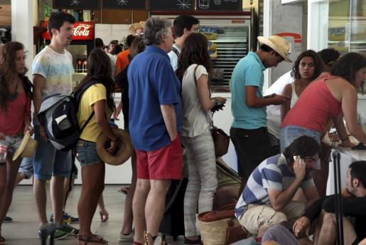 Un grupo de pasajeros espera frente a la ventanilla de la compañía.