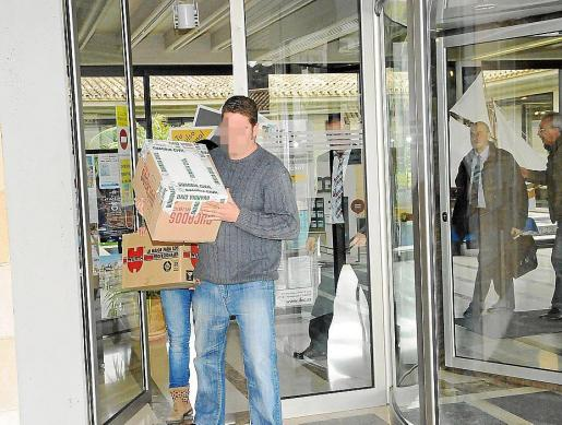 Varios agentes salen con cajas de documentación del Ajuntament de Calvià.