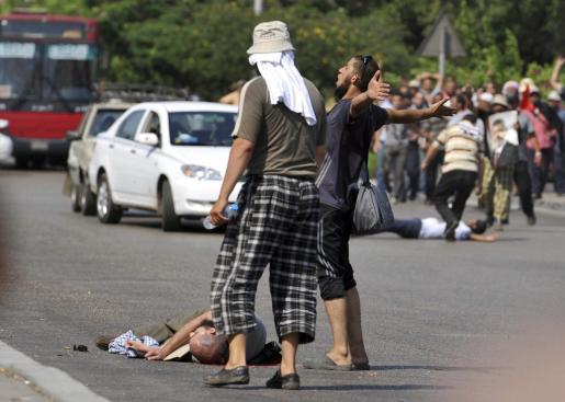 SAB11. EL CAIRO (EGIPTO), 05/07/2013.- Un simpatizante del presidente depuesto Mohamed Mursi yace muerto en el suelo tras ser disparado por el Ejército egipcio durante una manifestación frente a la sede de la Guardia Republicana en El Cairo, Egipto, el 5 de julio del 2013. Al menos una persona ha muerto a causa de los disparos del Ejército egipcio contra los seguidores de Mursi. Los islamistas han salido hoy a las calles para protestar contra el golpe de estado perpetrado el pasado miércoles por el Ejército