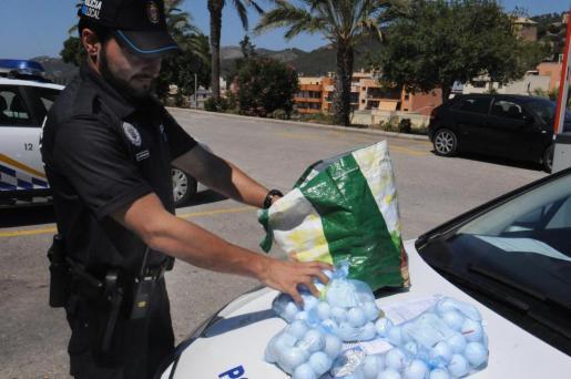 Un agente con varios paquetes con bolas de golf intervenidas al detenido.