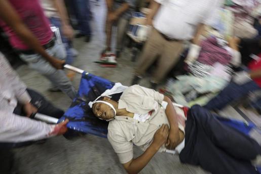 Activistas de los Hermanos Musulmanes evacúan el cadáver de un simpatizante del depuesto presidente egipcio Mohamed Mursi durante un enfrentamiento entre simpatizantes del depuesto presidente y las fuerzas de seguridad en El Cairo (Egipto) hoy, lunes 8 de julio de 2013.