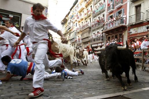 Varios mozos caen, en la curva de Mercaderes, ante los toros de la ganadería madrileña de Victoriano del Río que han protagonizado el cuarto encierro de los sanfermines.