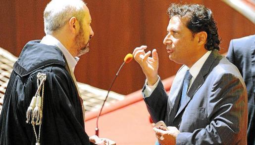 Francesco Schettino habla con su letrado durante la primera sesión del juicio.