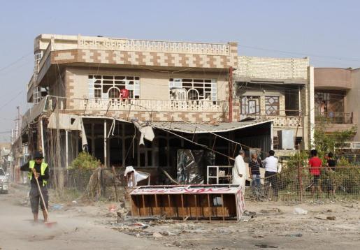 Unos trabajadores limpian uno de los lugares en los que ha explotado un coche bomba.