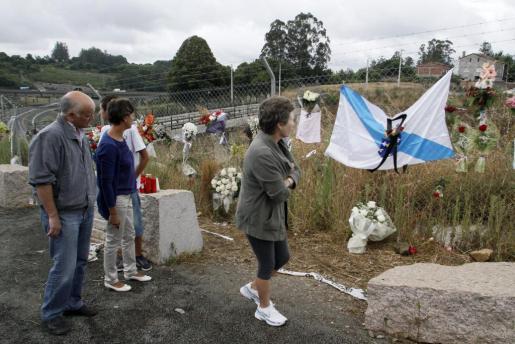 Varias personas observan las flores y las banderas con el crespón negro colocadas junto a la zona de la vía donde el pasado miércoles descarriló un tren Alvia.