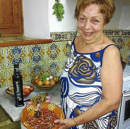 Coloma Mascaró posa junto a un plato de tomates asados con arenques y Oli de Mallorca DO