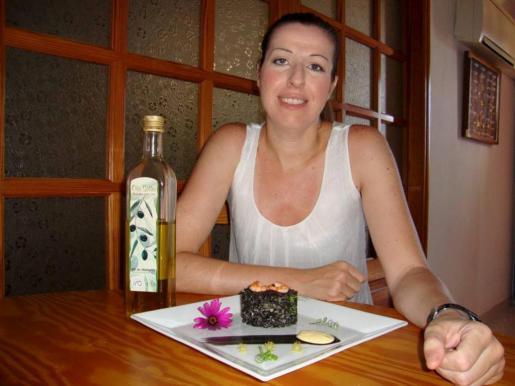 Silvia Caro posa con su receta de arroz negro con sepia y gambas y Oli de Mallorca D.O., muy bien presentada.
