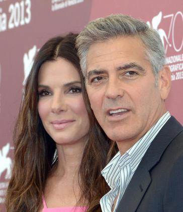 """Los actores estadounidenses George Clooney (d) y Sandra Bullock (i), posan durante el pase gráfico de la presentación de la película """"Gravity"""" en el Festival de Venecia."""
