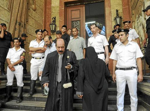 Un abogado (c) sale del tribunal mientras unos soldados hacen guardia en El Cairo tras ilegalizar a los Hermanos Musulmanes.