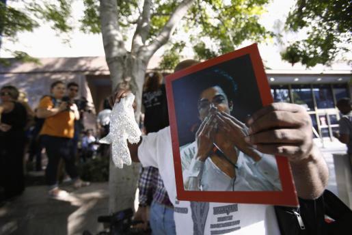 Un fan sujeta una foto de Michael Jackson mientras espera el veredicto del jurado.